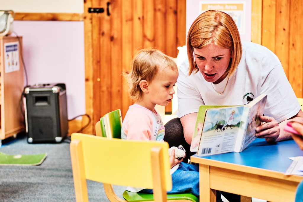 colour photograph of a toddler and teacher reading a story in a nursery school