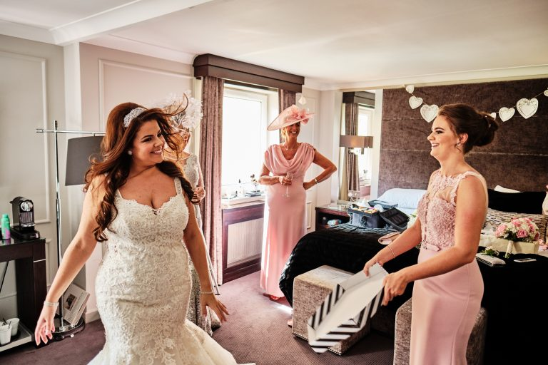 colour photograph of a bride being fanned by her bridesmaid during bridal preparation