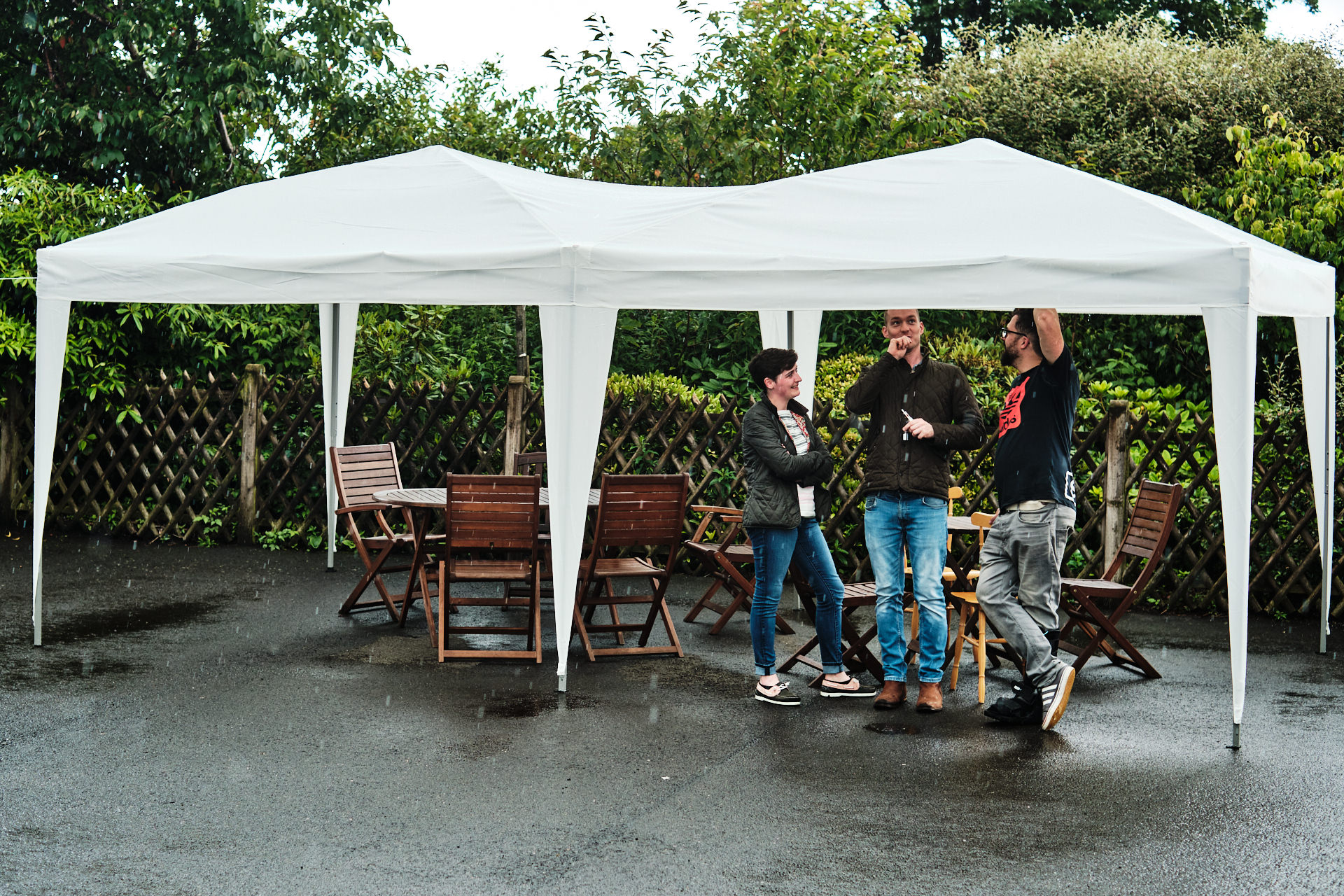 colour photograph of the groom and wedding guests sheltering from the rain under a gazebo