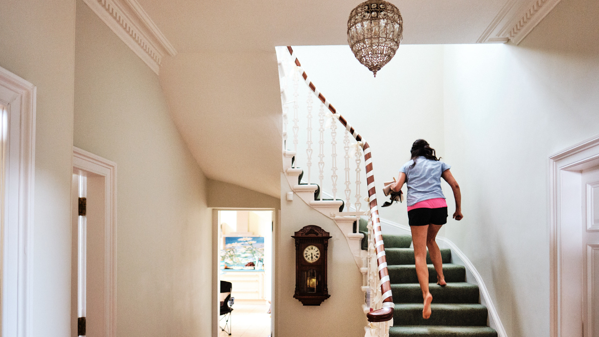 colour photograph of a woman wearing shorts running upstairs in a house