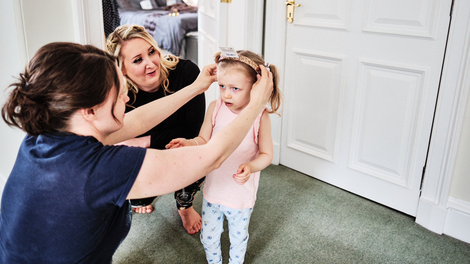 a young flower girl having a hairband fitted by her mum before the start of a wedding