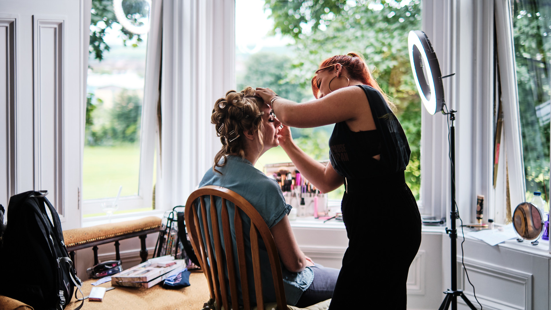 a colour photograph of a bride having her make up applied before her wedding