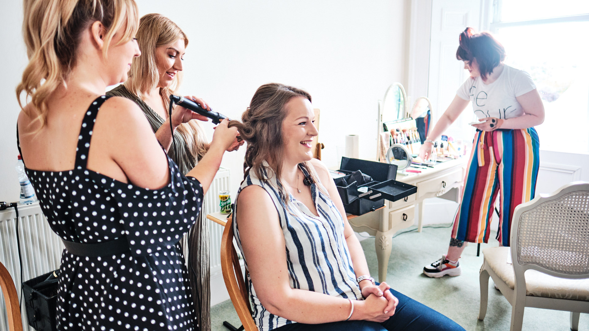 A colour photograph of a bridesmaid having her hair styled before a wedding