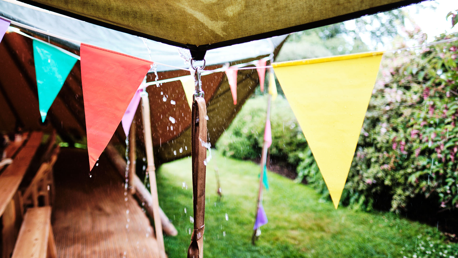 a colour photograph of rain running down the roof of a tipi being used for a wedding