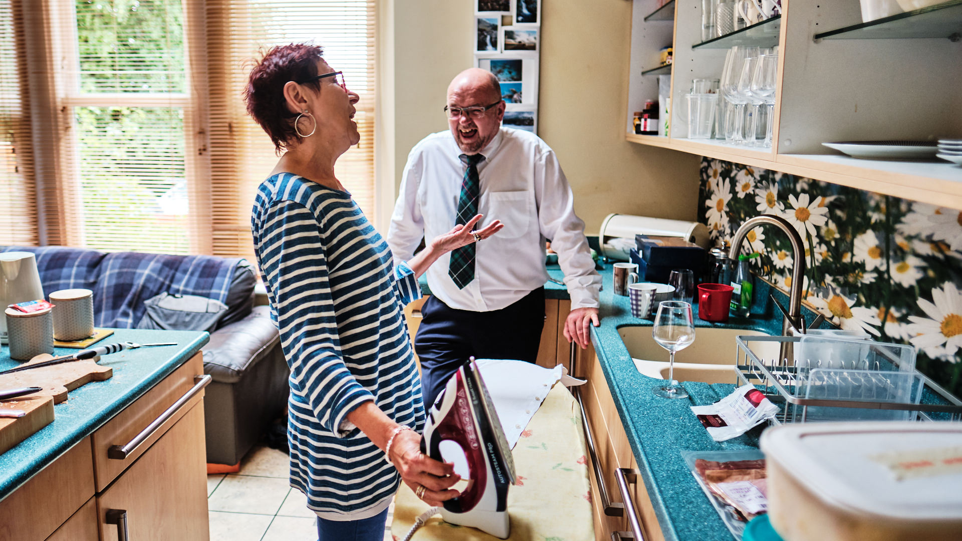 Colour photograph of wedding guests ironing clothes and laughing as they get ready for the wedding day