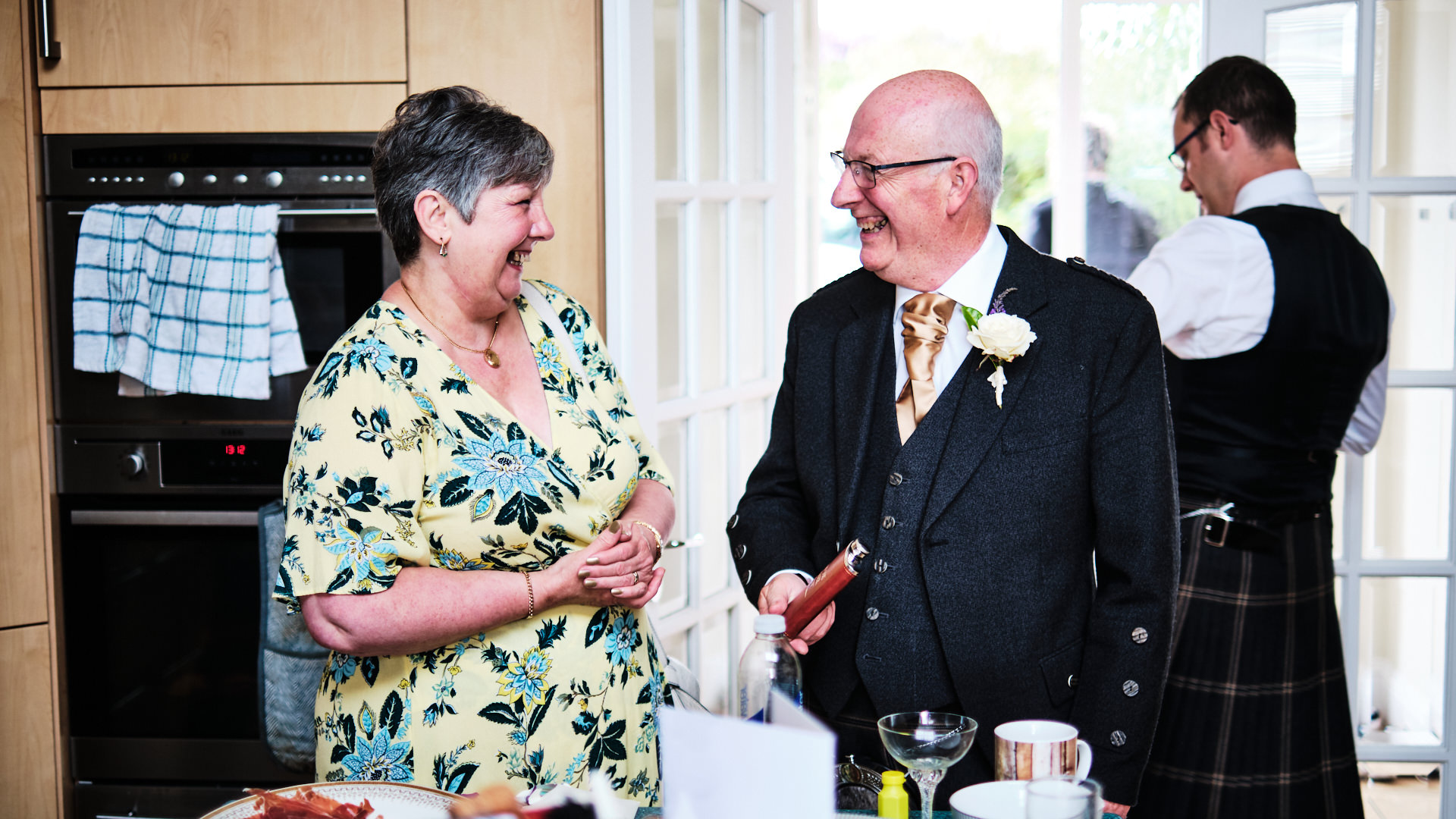 colour photograph of the  father of the bride laughing with one the guests on the morning of his daughter's wedding