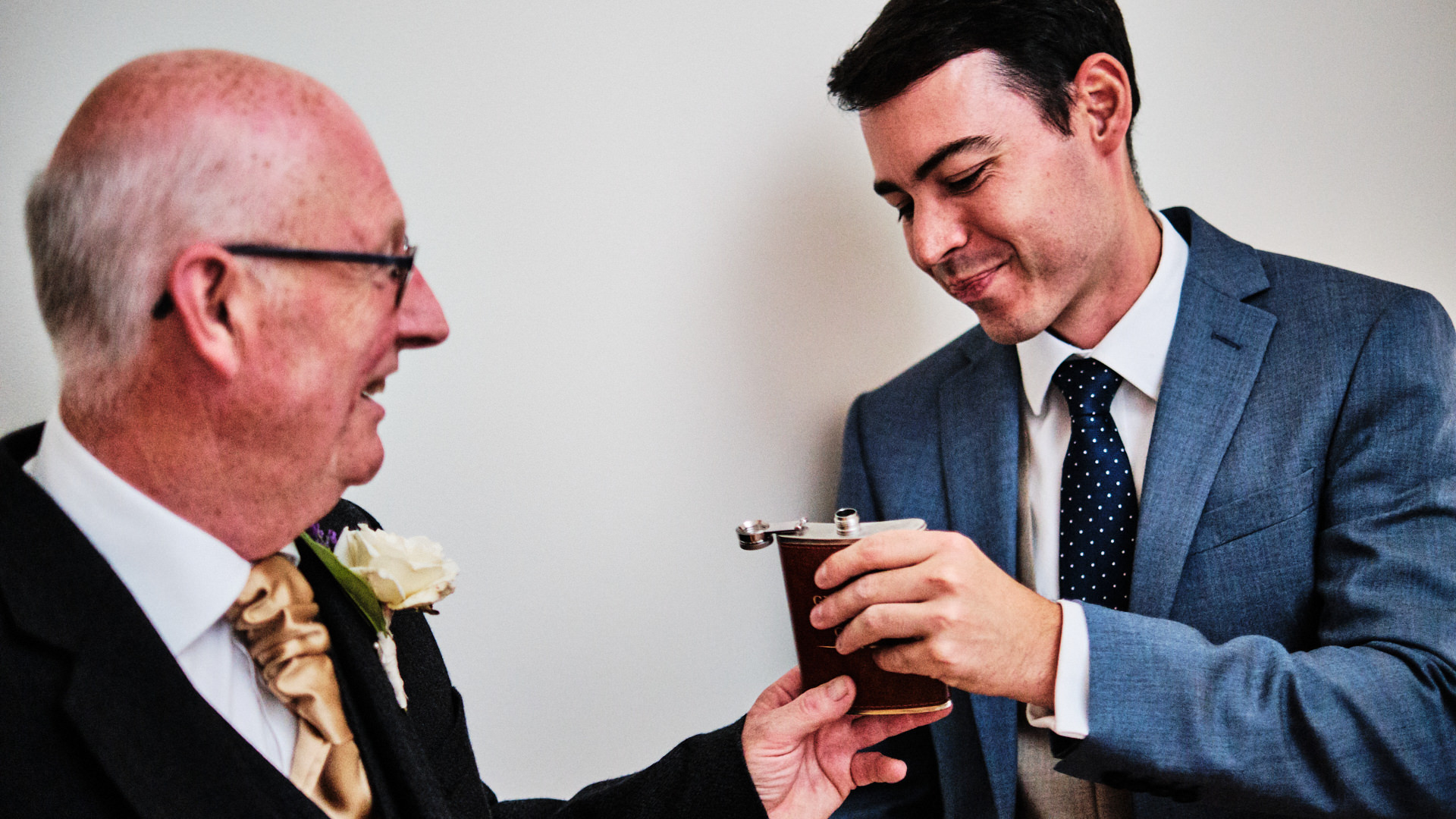 A colour photograph of a wedding guest and the father of the bride sharing a drink from his hip flask before his daughter's wedding