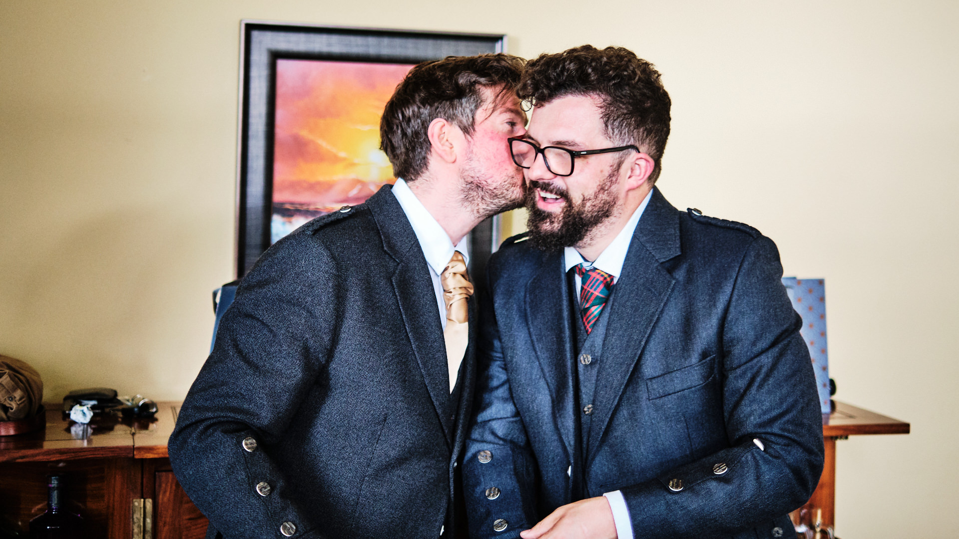 a colour photograph of the best man giving the bridegroom a kiss open the cheek as they are getting ready for the wedding day
