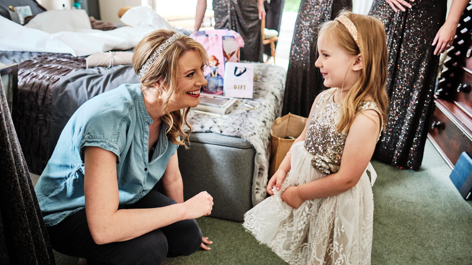 Colour photograph of a bride chatting and smiling to her flower girls as they get ready for the wedding