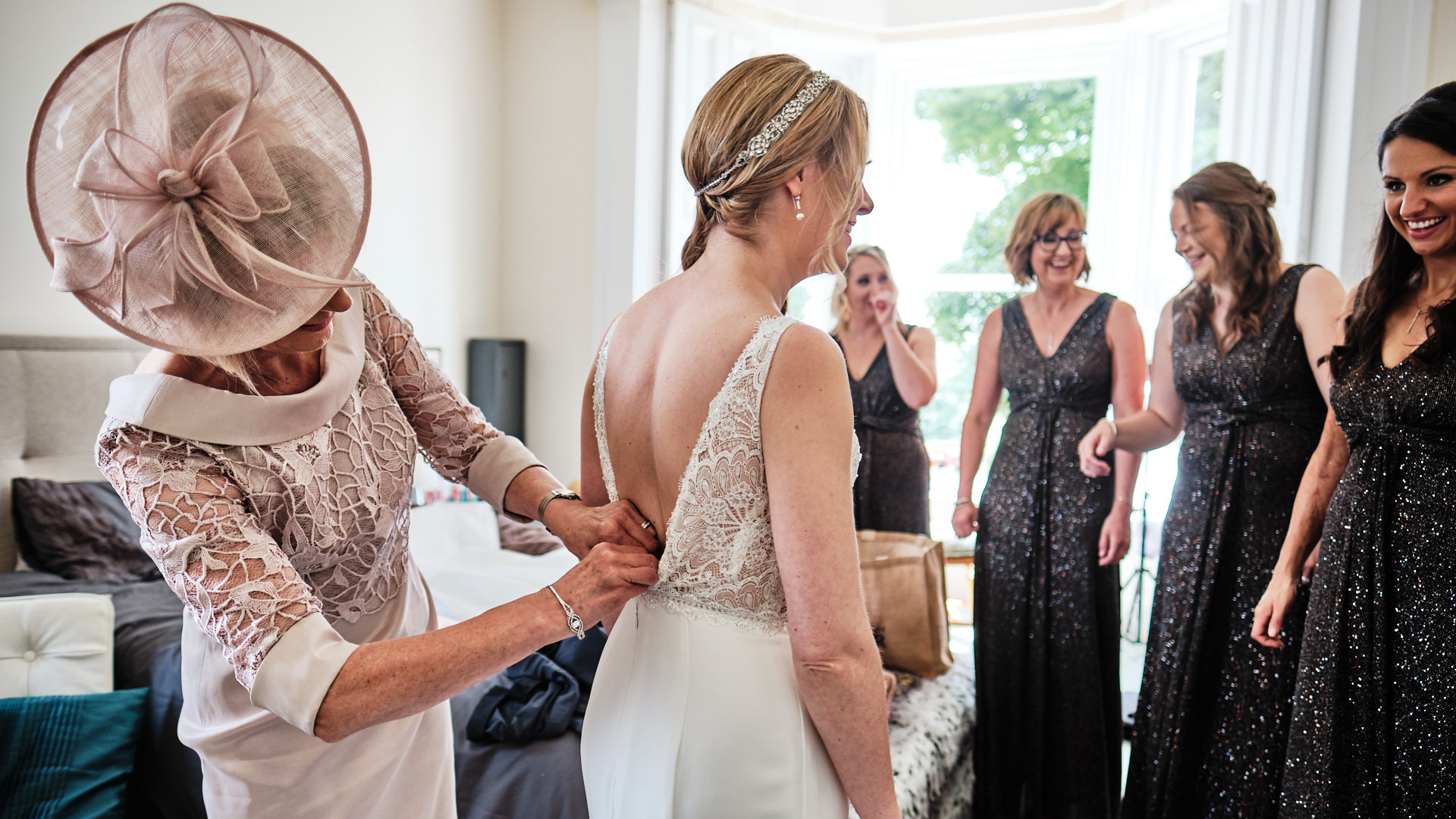 colour photograph of a the mother of the bride fastening up the back of her daughter's wedding dress before the wedding