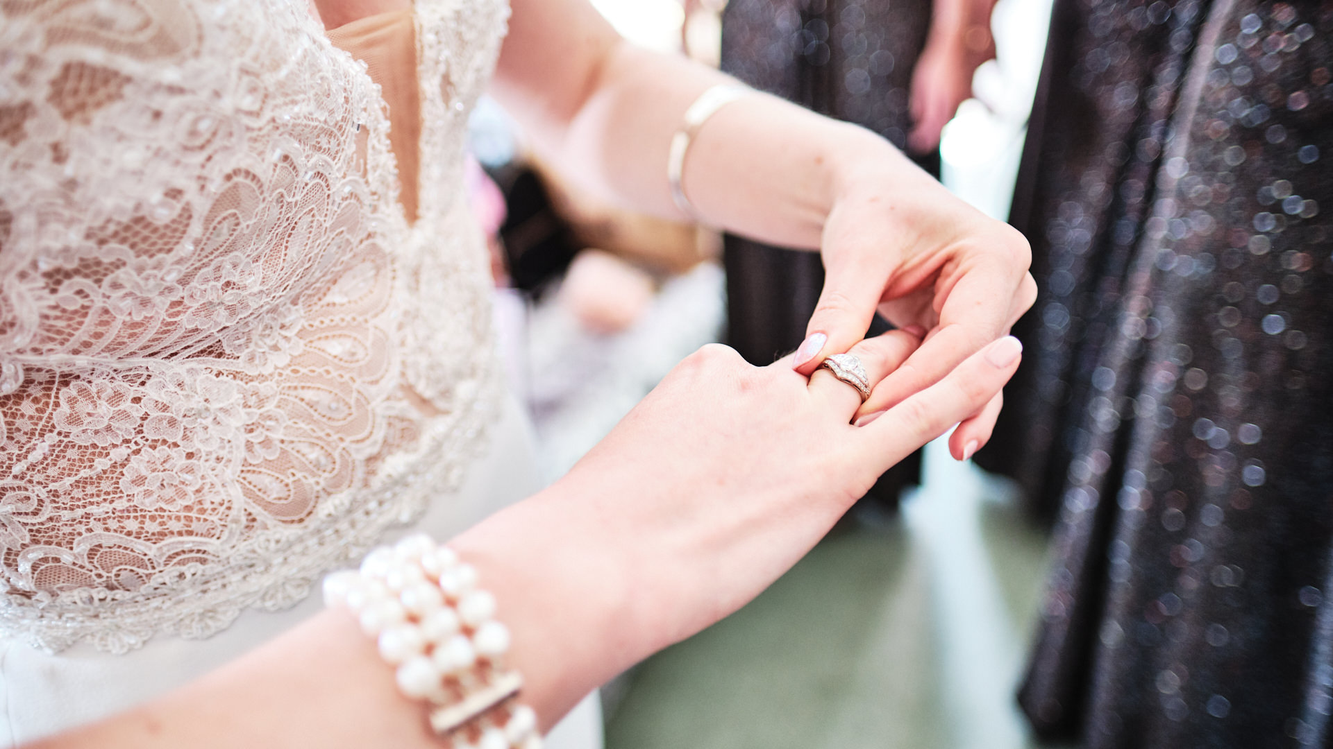 colour photograph of a bride moving her engagement ring to her right hand before her wedding