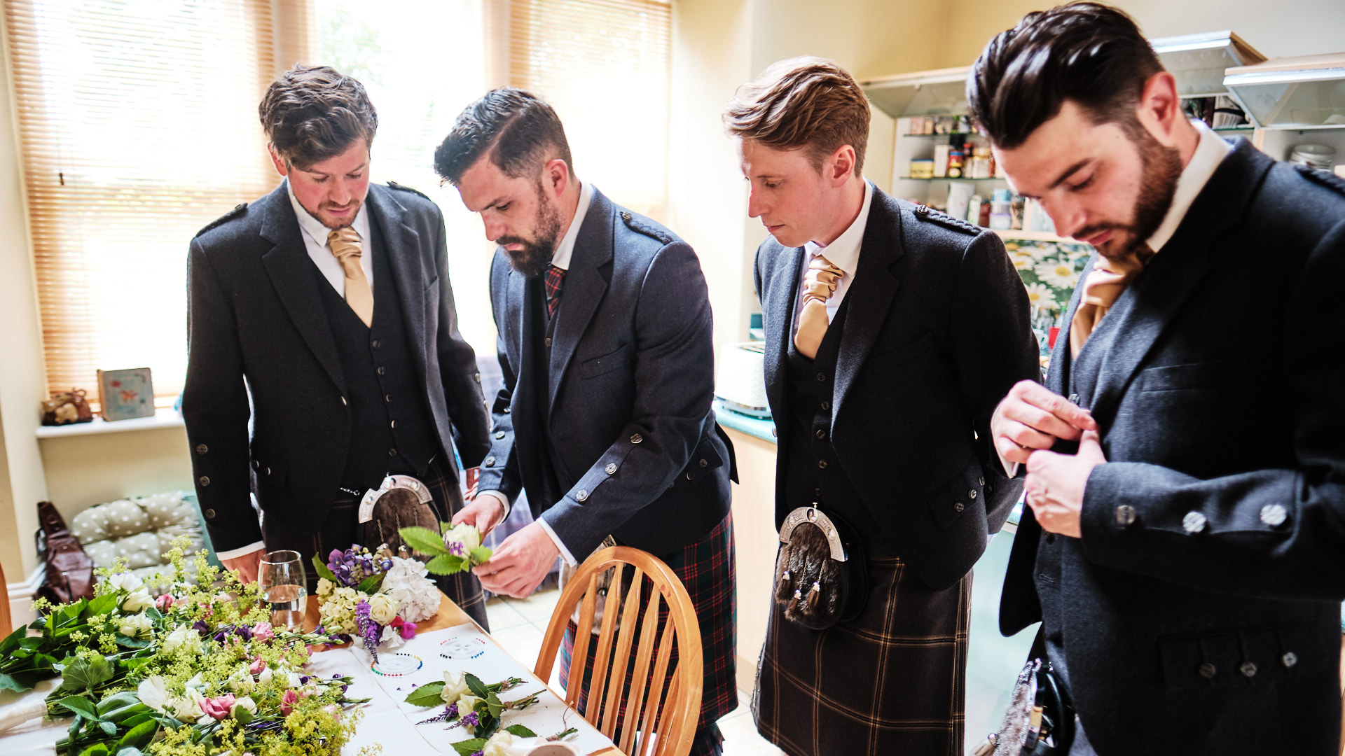 a colour photograph of the bridegroom and how groomsmen putting their buttonhole flowers on