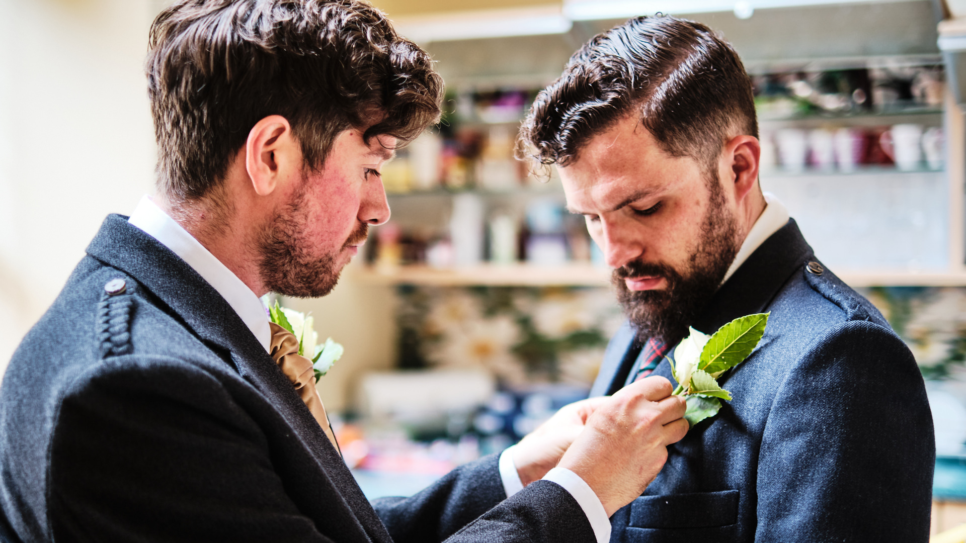 a colour photograph of the batsman putting the bridegroom's button hole flower on before the start of the wedding