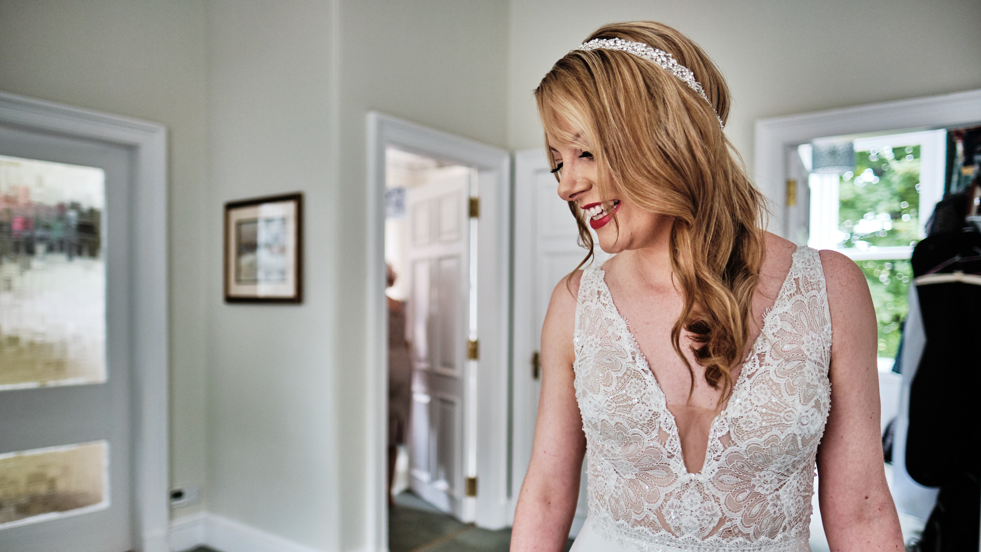 colour photograph of a bride smiling at her dad as he comes upstair to see her for the first time in her wedding dress