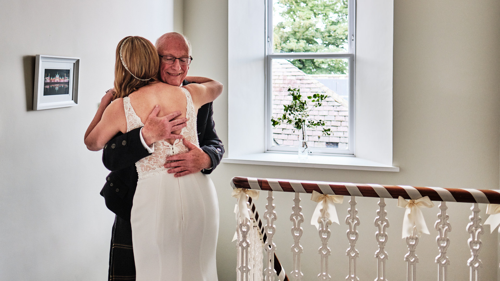 Colour photograph of the father of the bride cuddling her after seeing her in her wedding dress for the first time