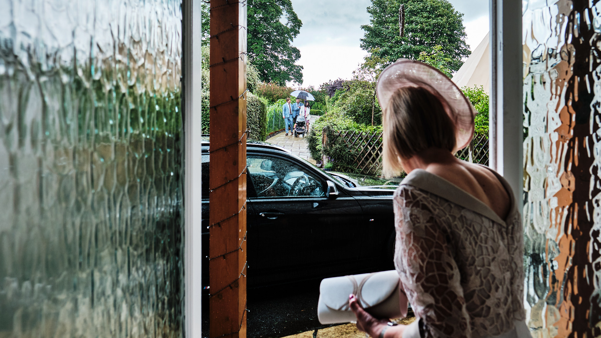 colour photograph of the mother of the bride watching wedding guests arriving in the rain prior to the start of the wedding