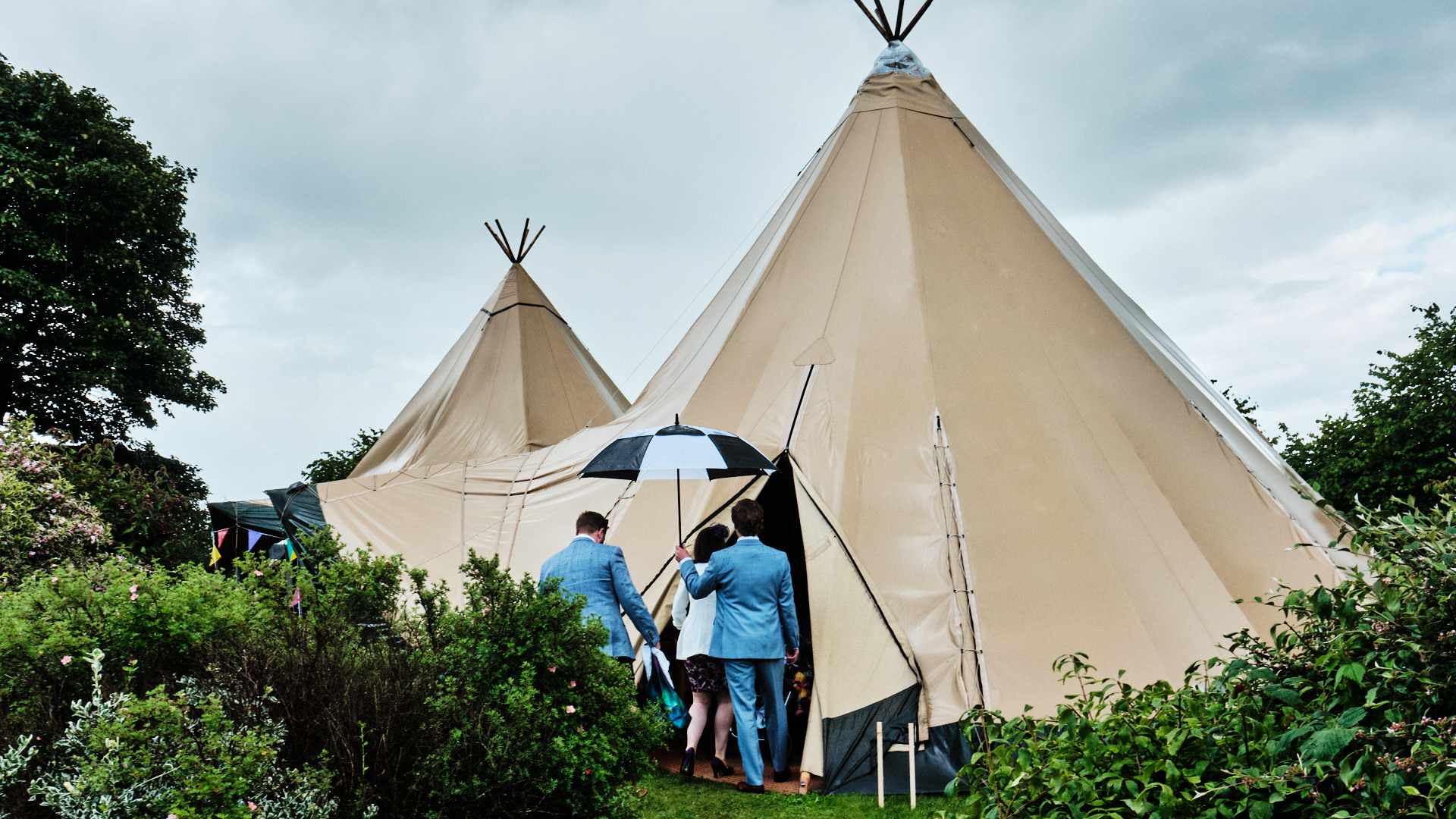 Colour photograph of a double tipi set up in a garden with people entering under umbrellas in the rain