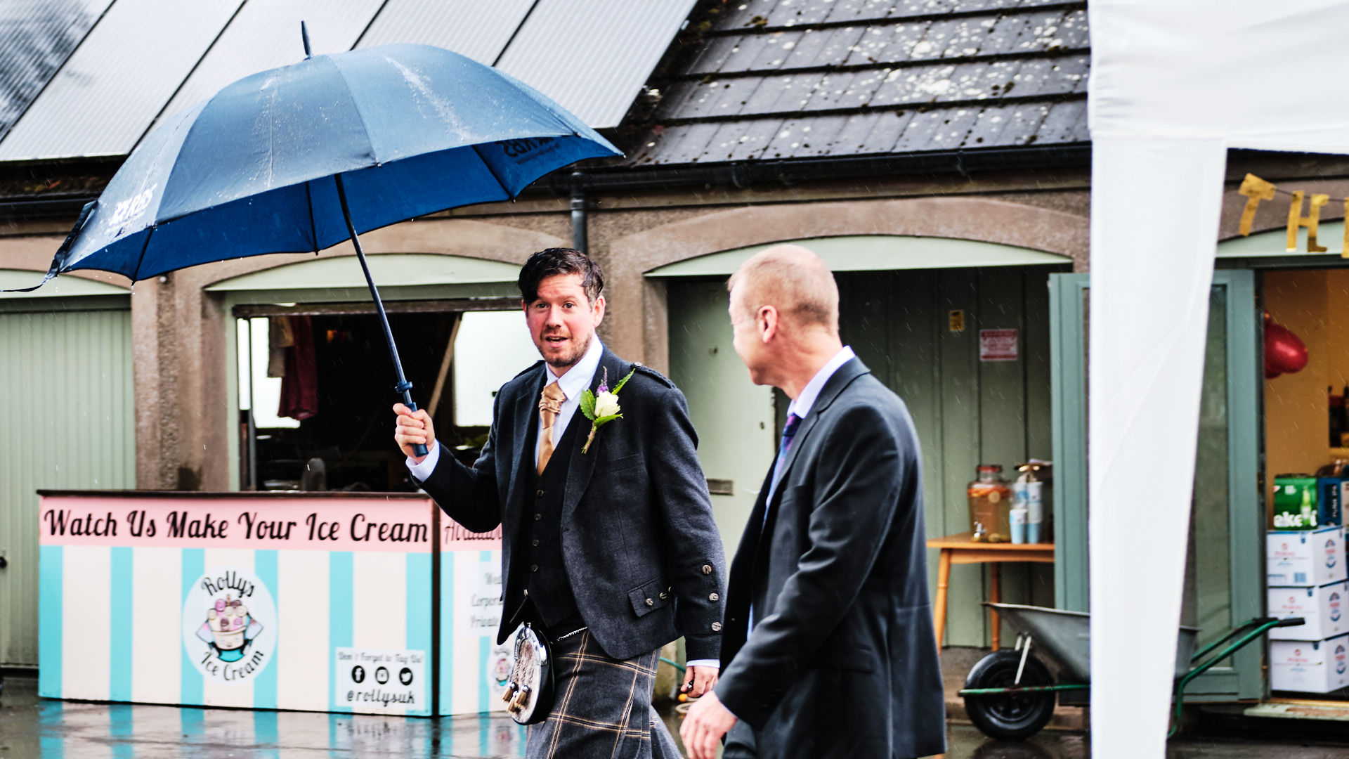 colour photograph of the bestman holding an umbrella just before the start of a wedding