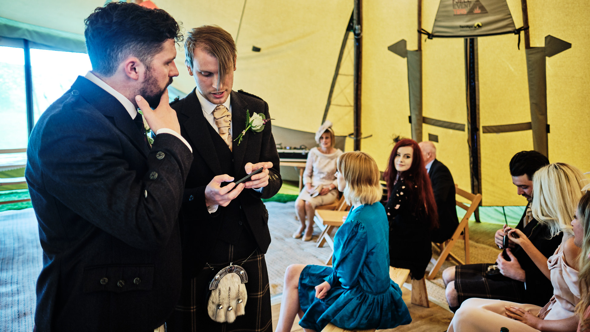 colour photograph of the bridegroom and an usher talking before the start of the wedding