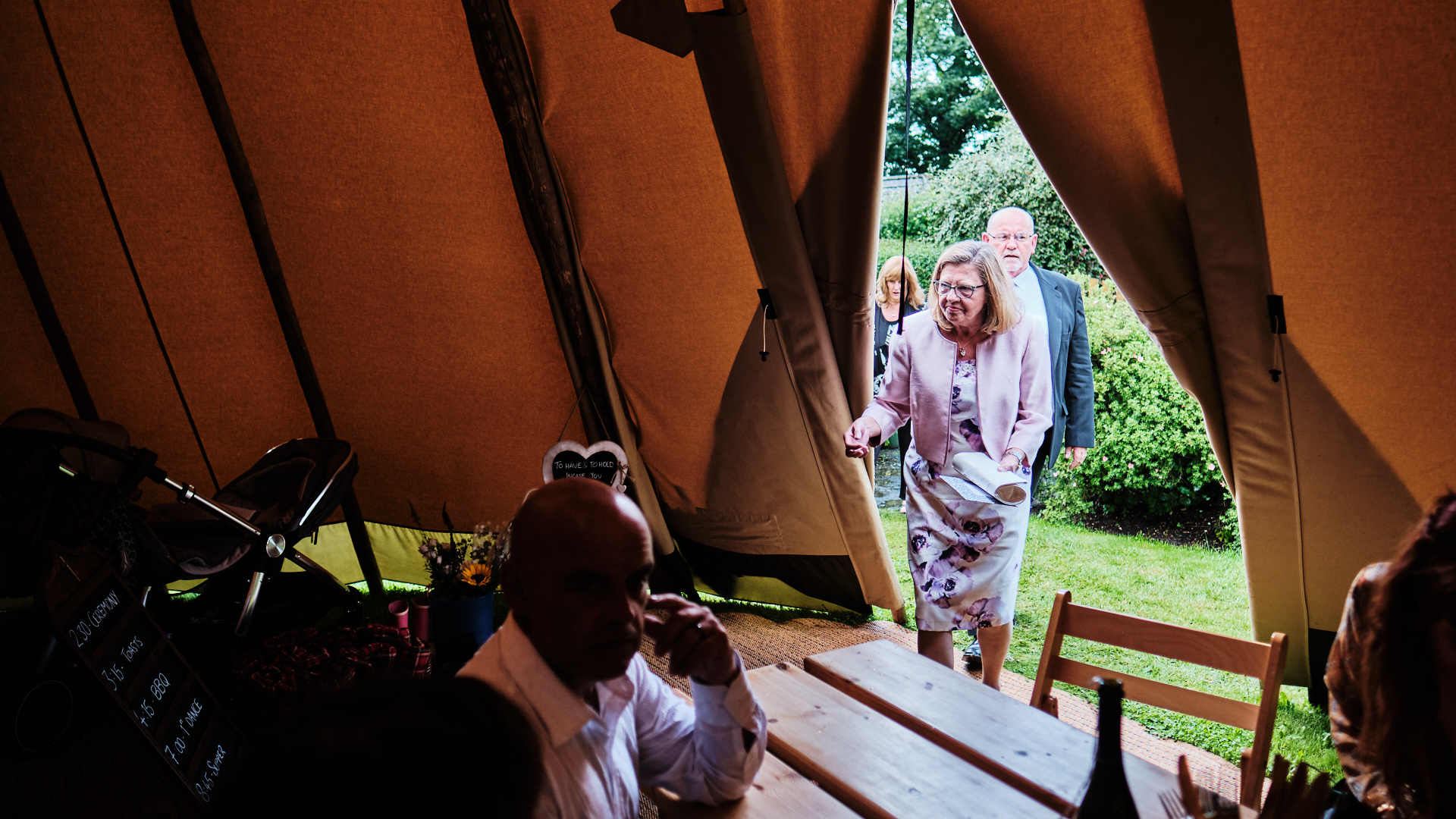 colour photograph of wedding guests arriving inside a tipi for a wedding