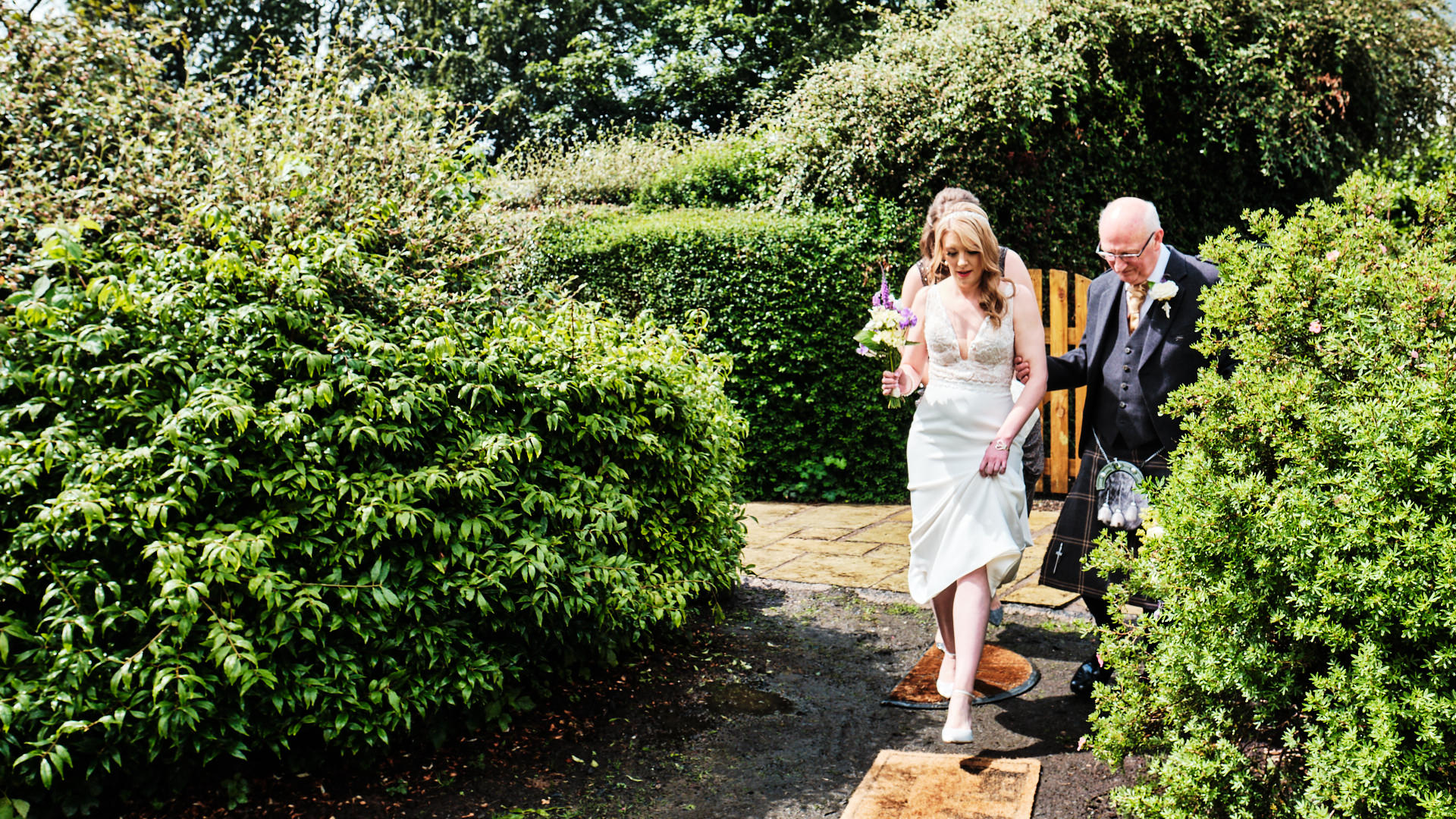 colour photograph of the bride and her dad walking to the wedding ceremony in her garden