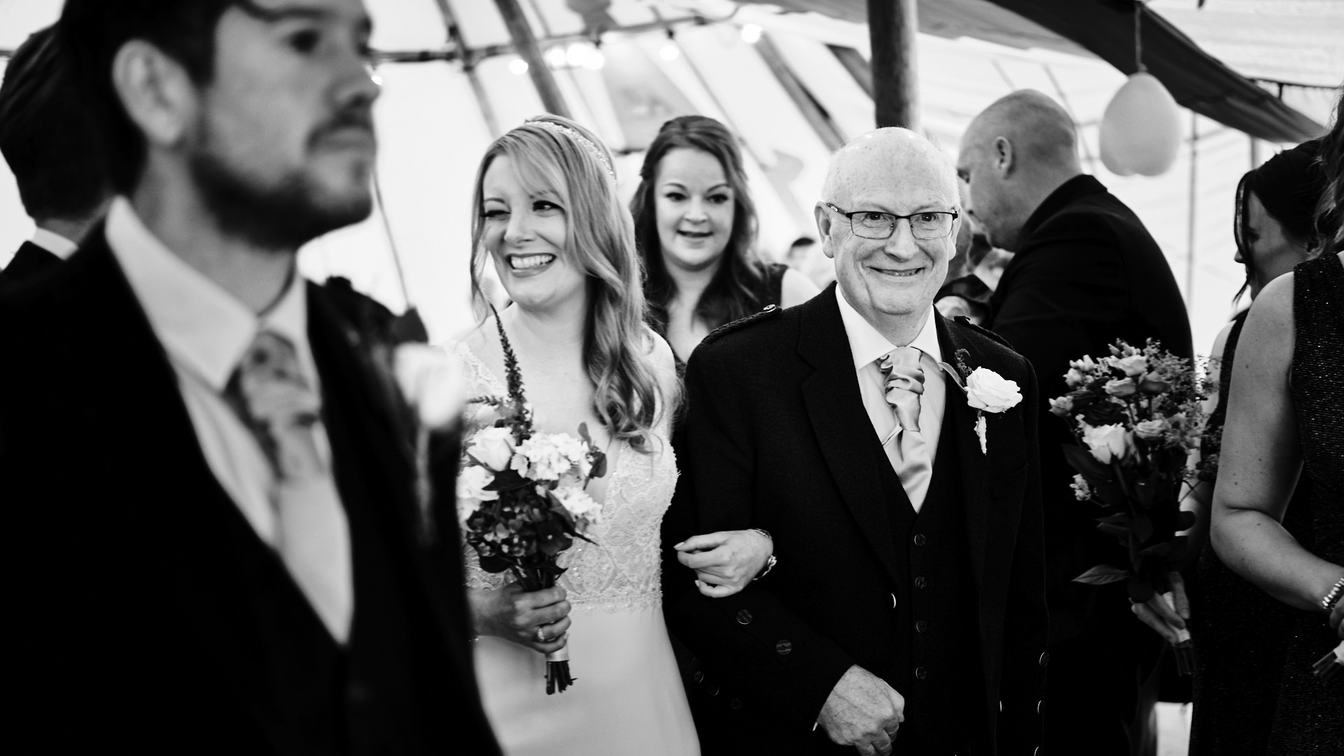 black and white photograph of a bride winking at a guest as she walk down the aisle at her wedding