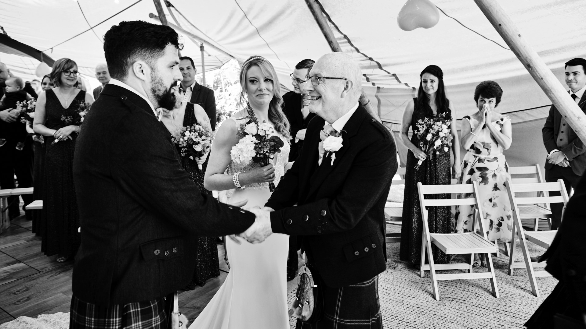 black and white photograph of the father of the bride shaking the groom's hand at the start of the wedding ceremony