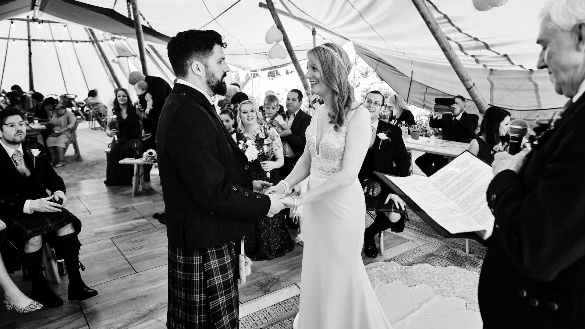 black and white photograph of the bride and groom holding in hands in front of all their wedding guests at the start of the wedding ceremony