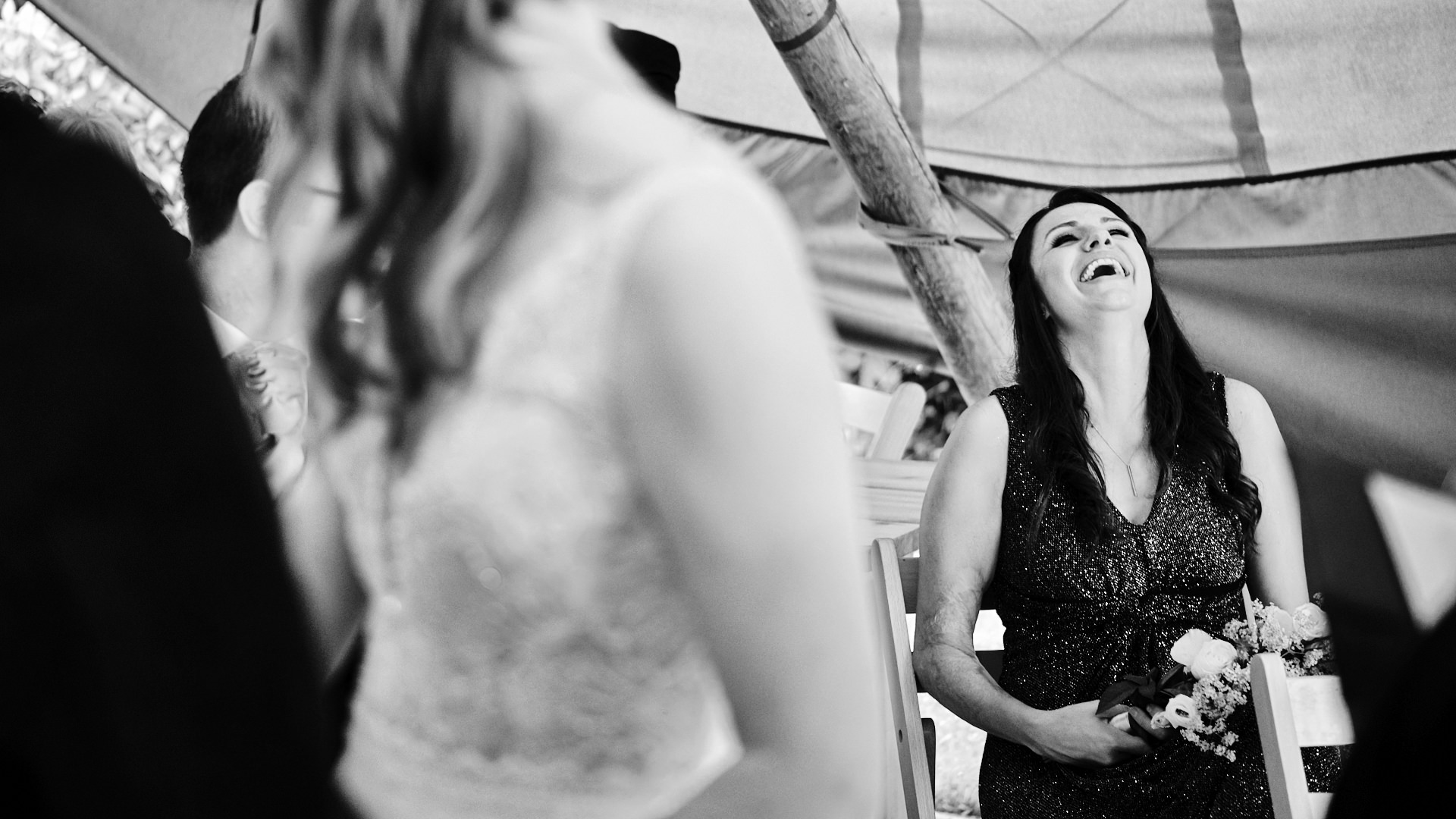 black and white photograph of a bridesmaid laughing during a wedding ceremony