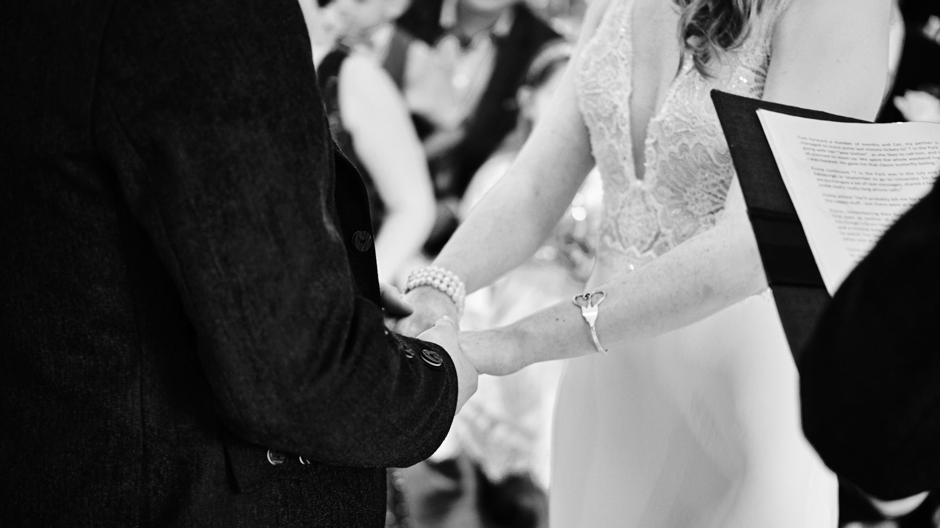 black and white close up photograph of the bride and groom holding hands during their wedding ceremony