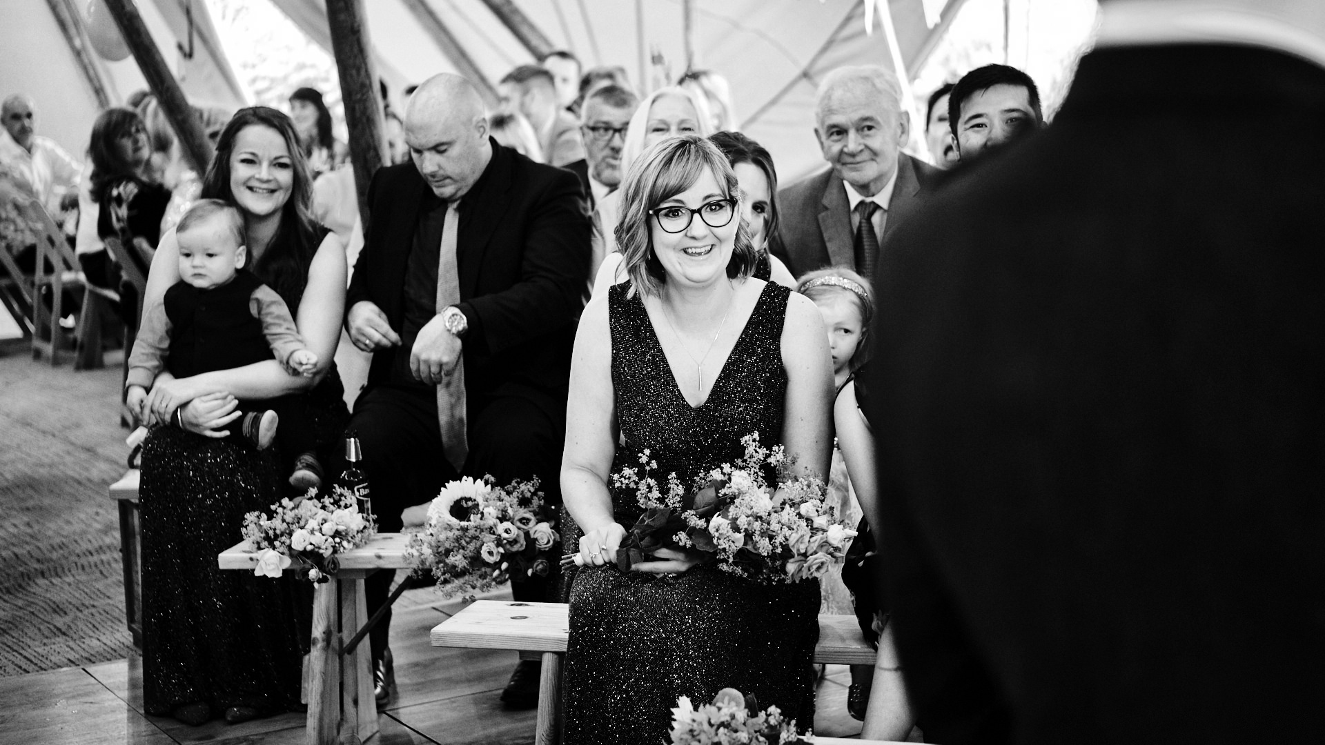 black and white photograph of a bridesmaid and guests smiling during a wedding ceremony