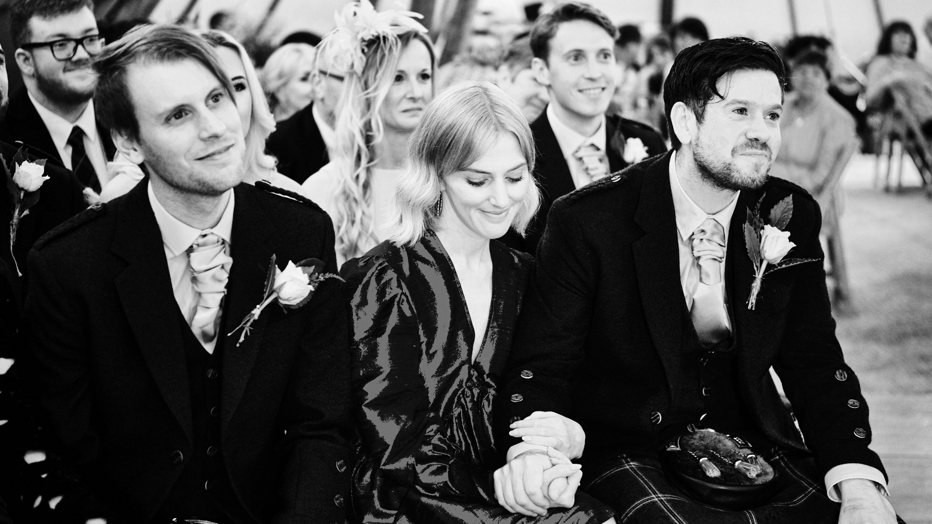 black and white photograph of a wedding guests smiling during a wedding ceremony