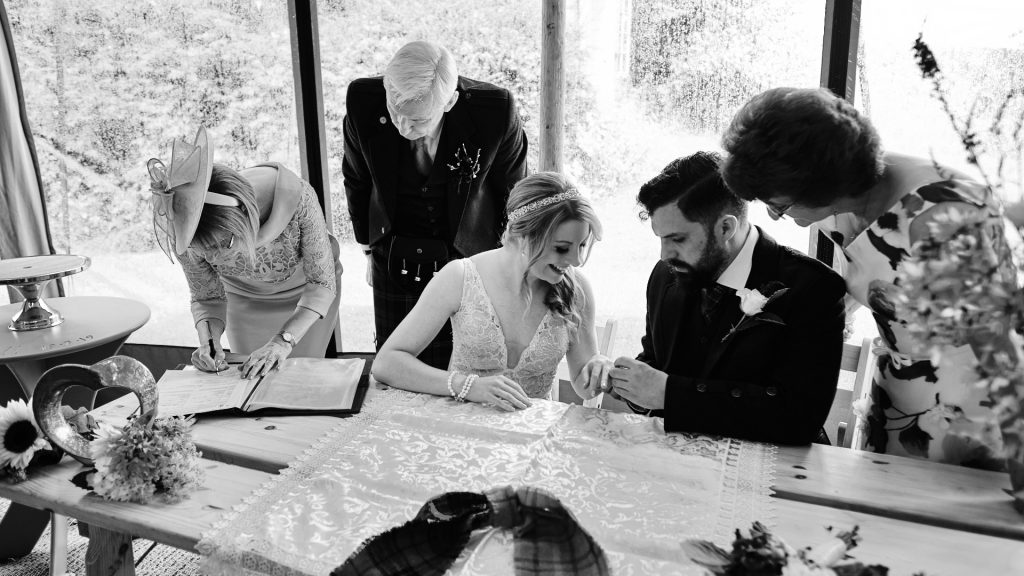 black and white photograph of a newly married couple during the signing of the reciter at their wedding