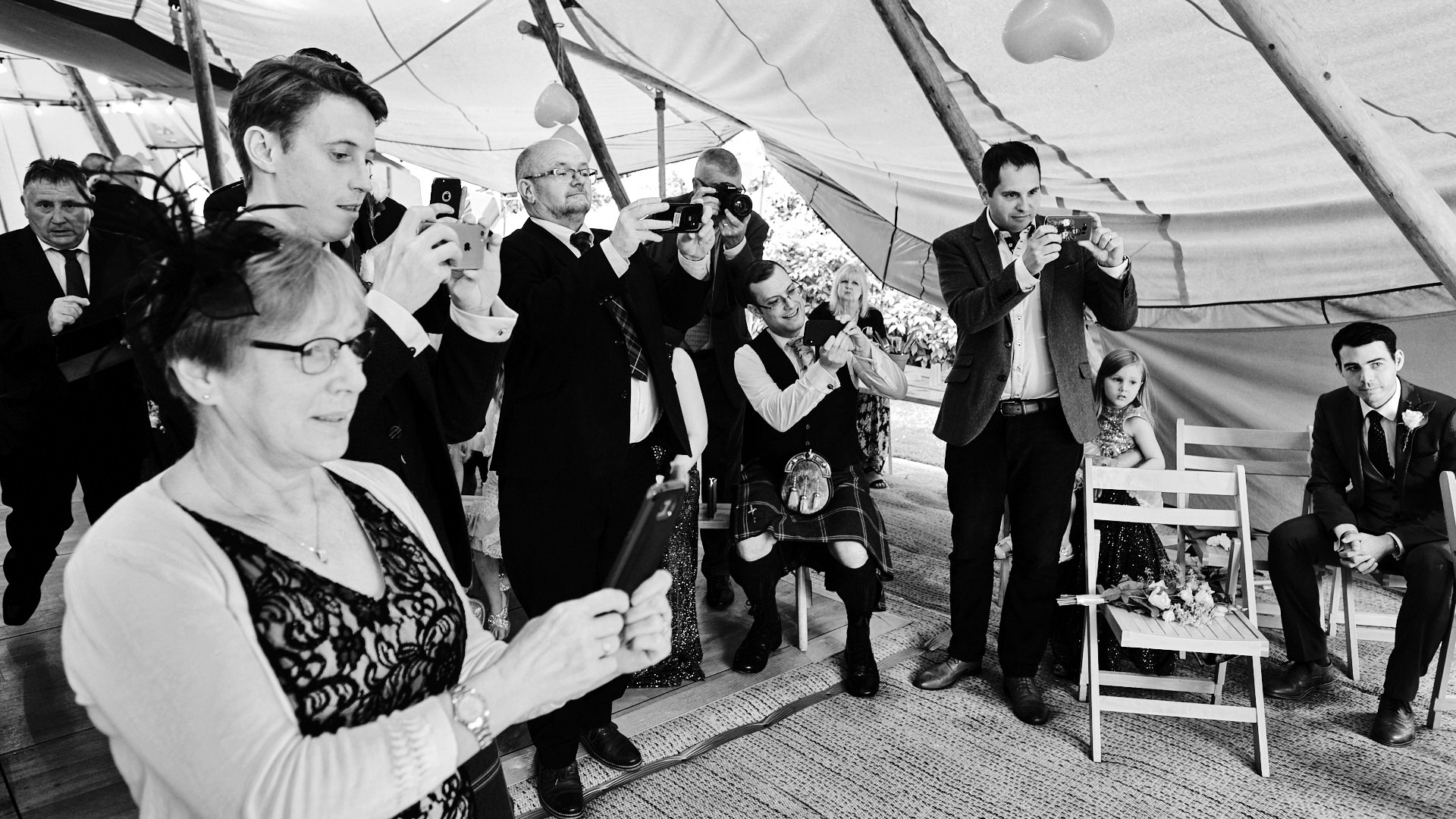 black and white photograph of wedding guests photographing the bridal party during the signing of the register