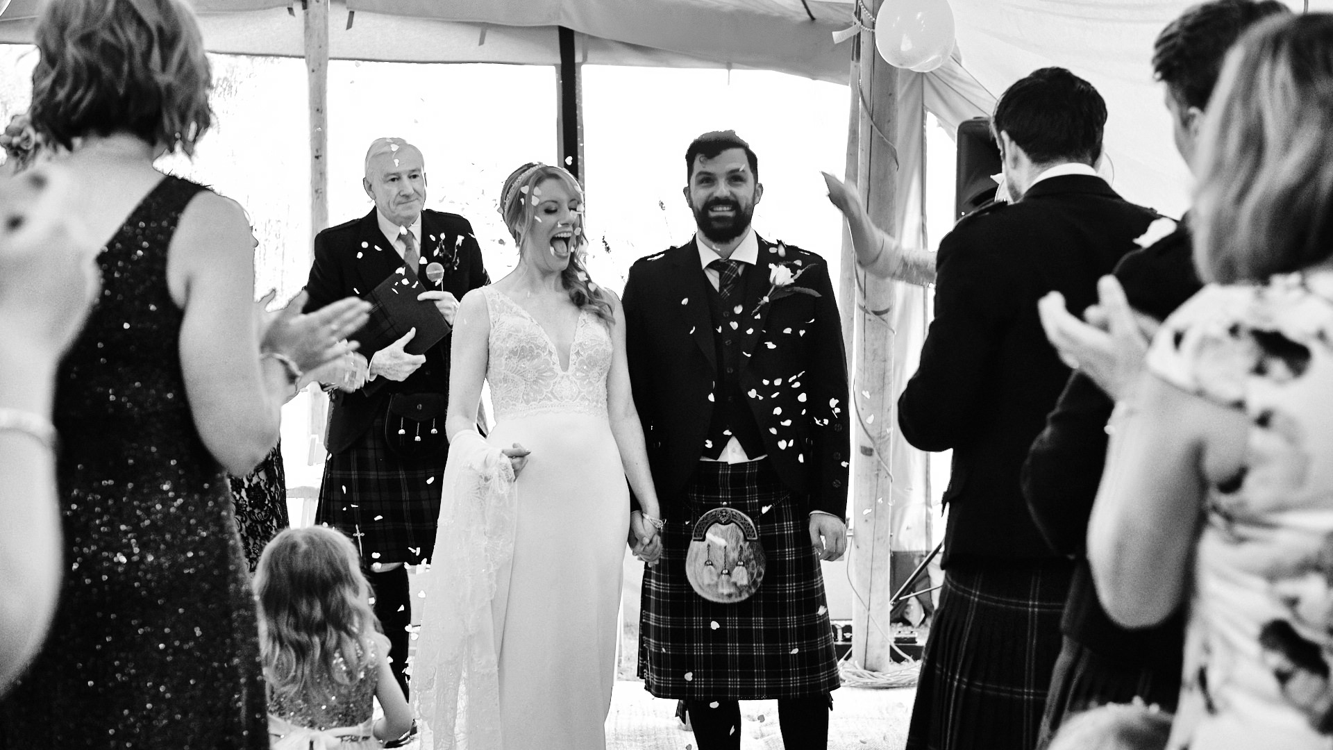 black and white photograph of confetti being thrown over the bride and groom as the walk back down the aisle at their wedding