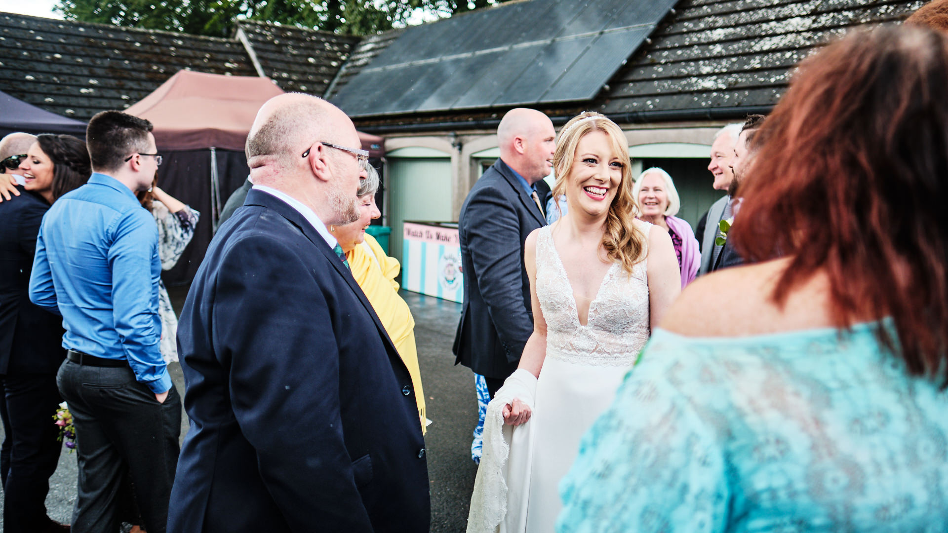 colour photograph of a smiling bride talking to her wedding guests