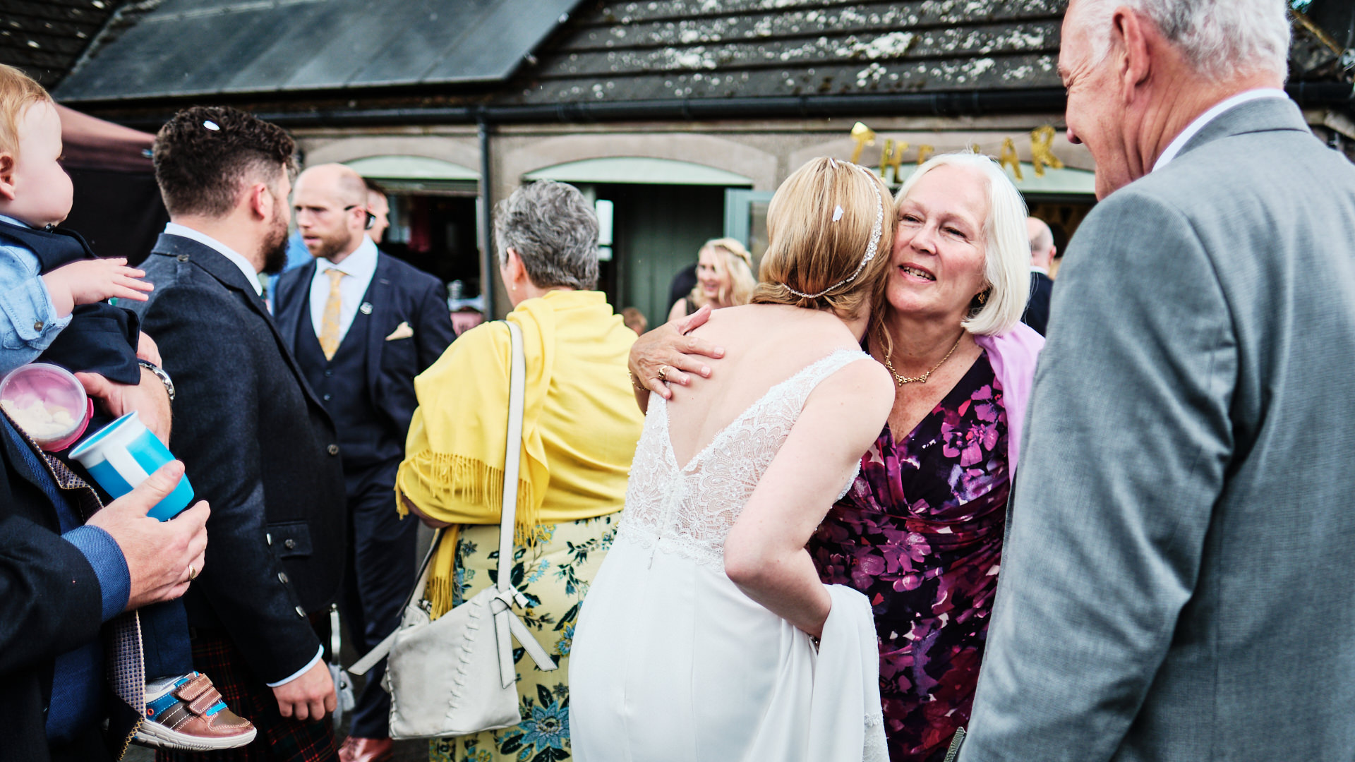 colour photograph of the bride hugging an older woman during her wedding day