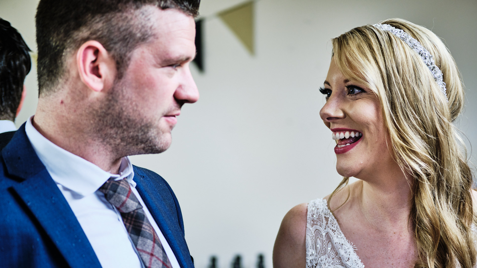 colour photograph of a smiling bride chatting to a male wedding guest during her wedding reception