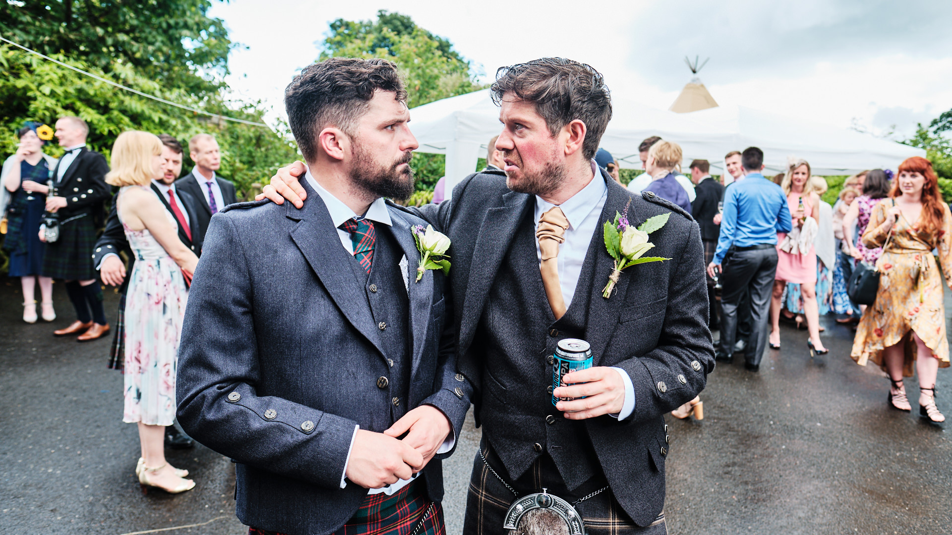 colour photograph of the bride groom and his best man standing in the rain after the wedding ceremony