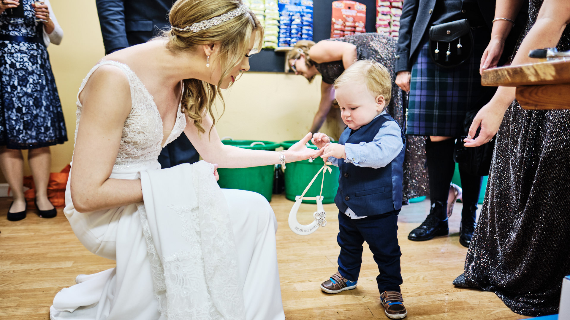 colour photograph of a toddler giving a horseshoe to a bride during her wedding