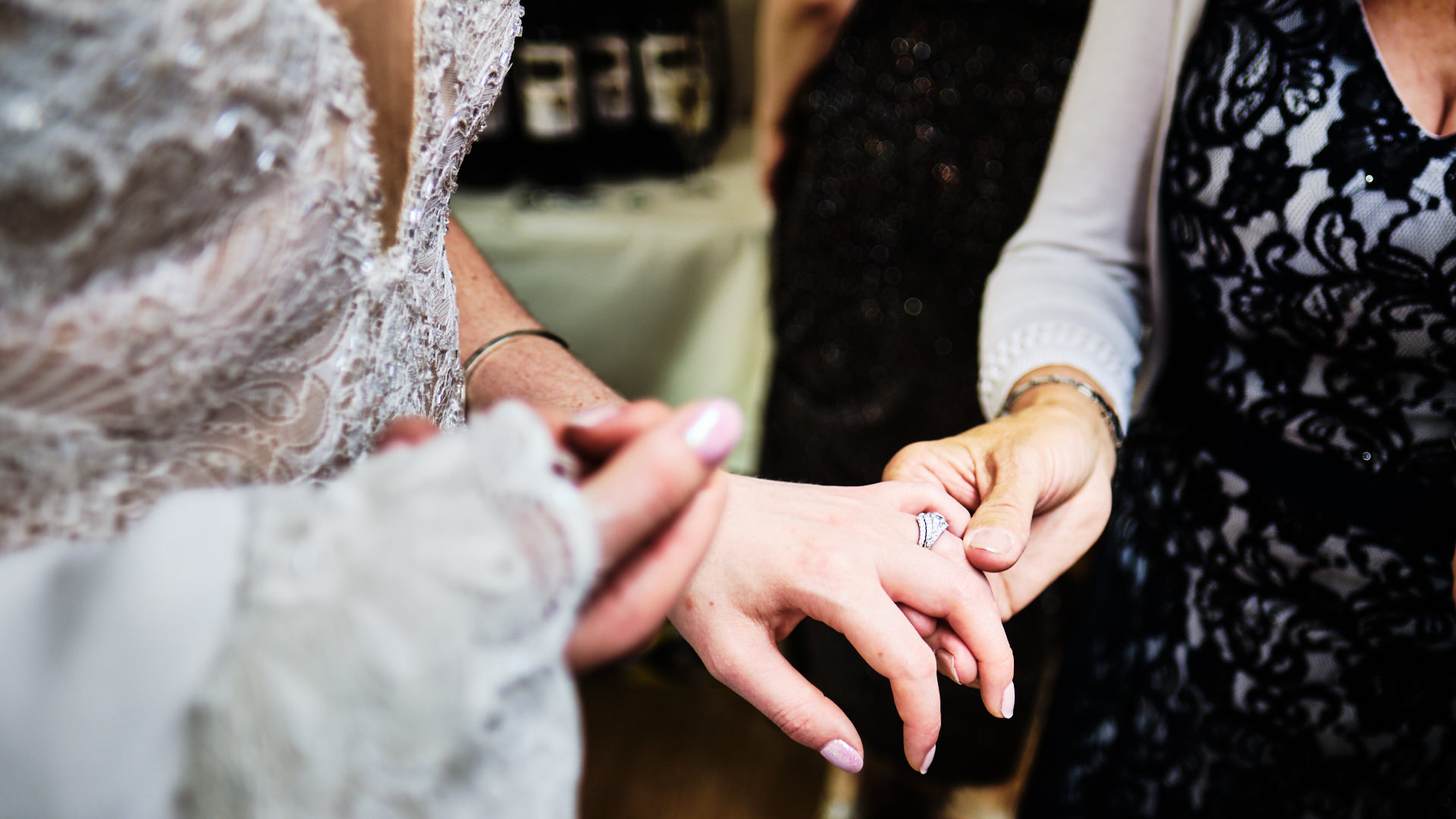 colour photograph of a female wedding guest holding the bride's hand to look at her wedding ring