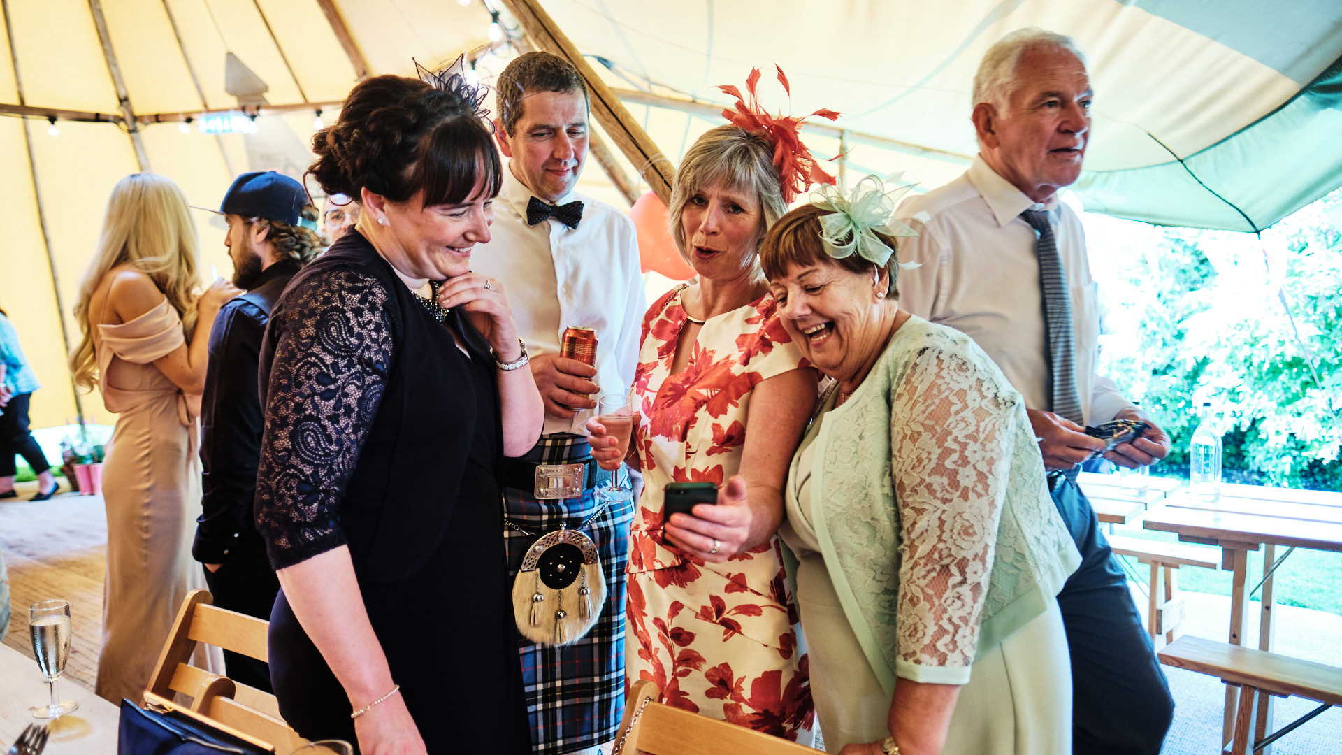 colour photograph of laughing wedding guests looking at a mobile phone
