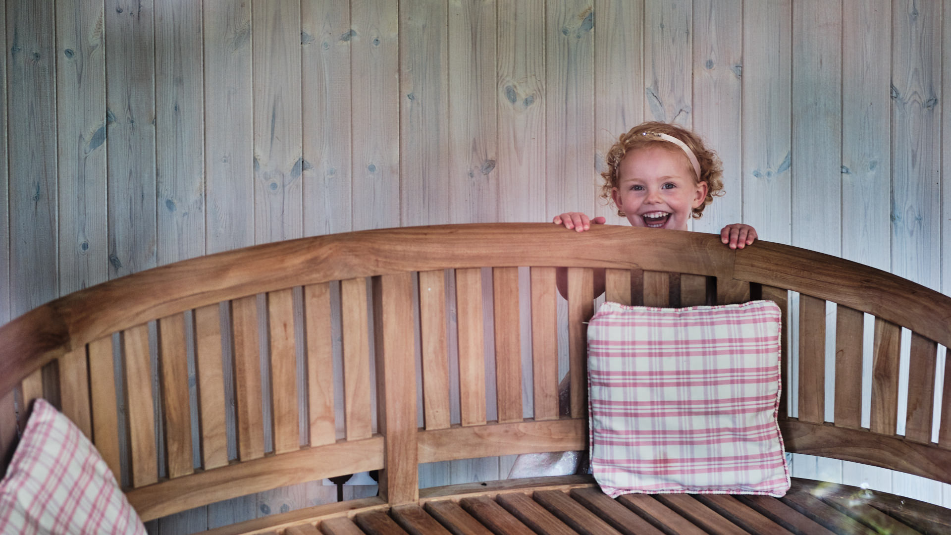 colour photograph of a small girl hiding behind a wooden bench and playing peekaboo