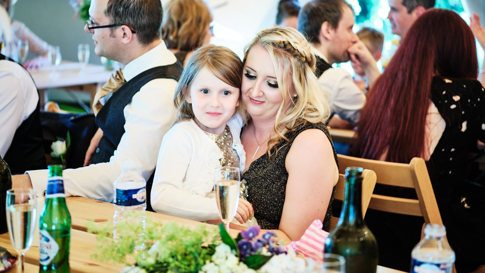colour photograph of a bridesmaid and her daughter smiling during the wedding reception