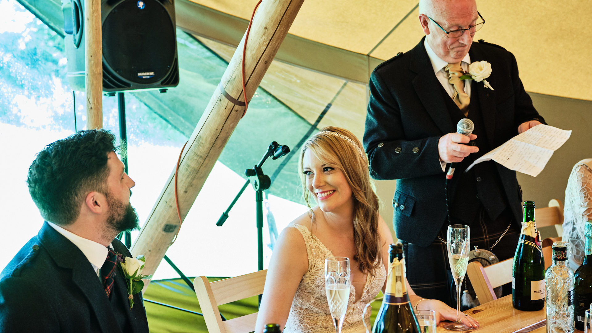 colour photograph of a bride and groom sharing a private moment during her father's speech at his daughter's wedding