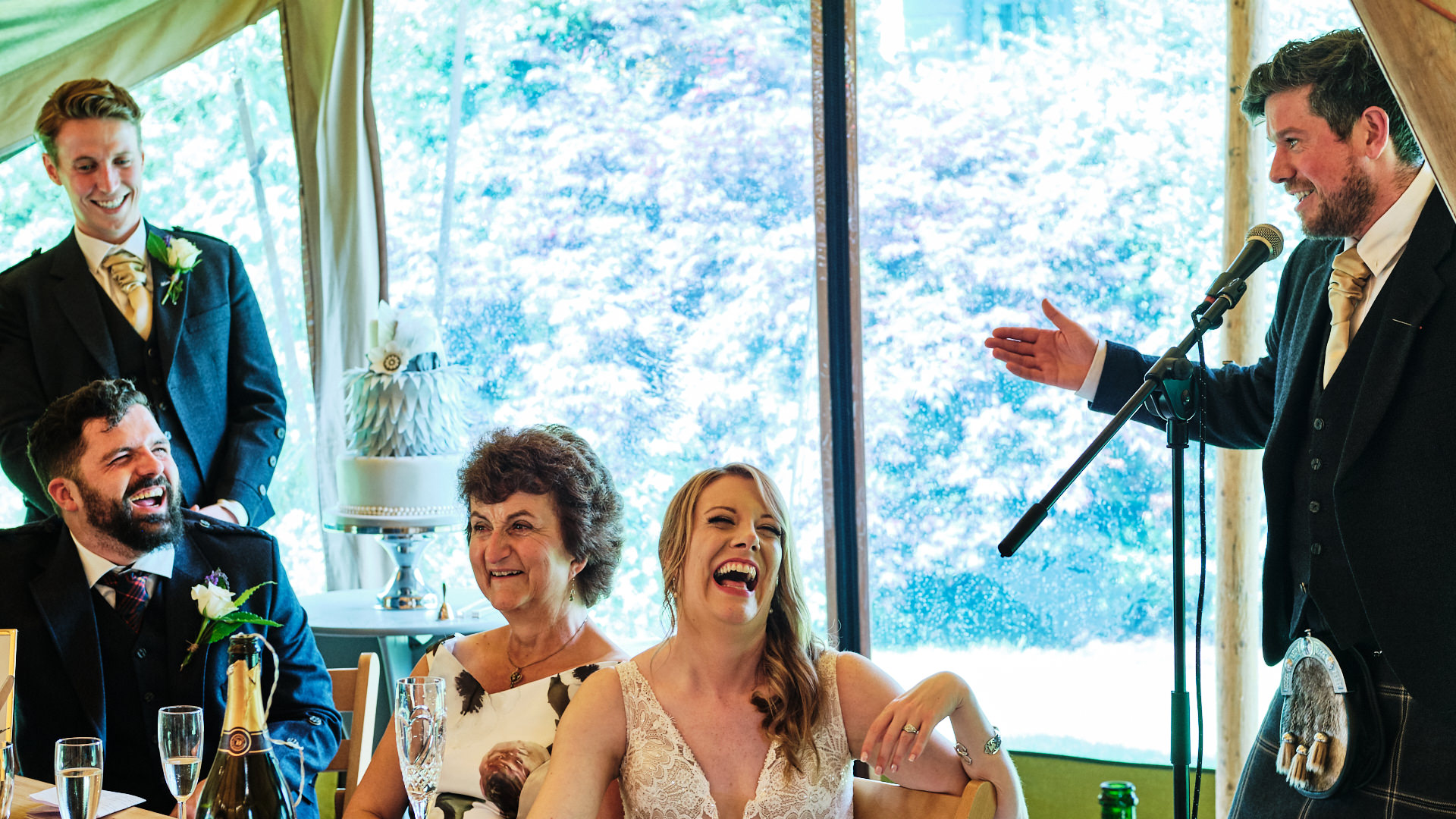 colour photograph of the best man  giving a speech at a wedding while the wedding party are laughing