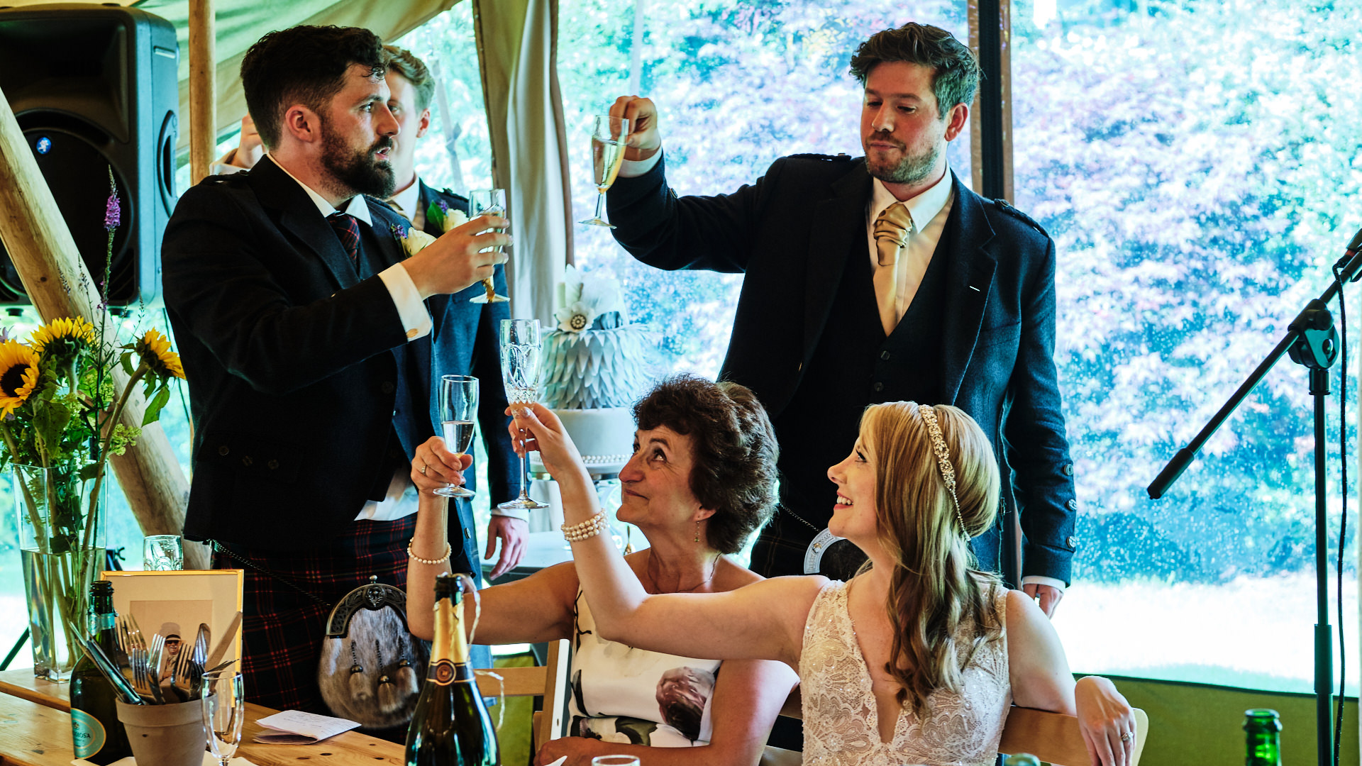 colour photograph of the best man  giving a toast to the bride and groom after his speech speech while the wedding party are raising their glasses