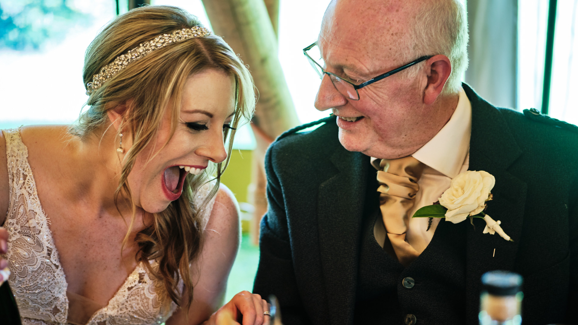 colour photograph of a bride and her dad sharing a joke during a speech at her wedding