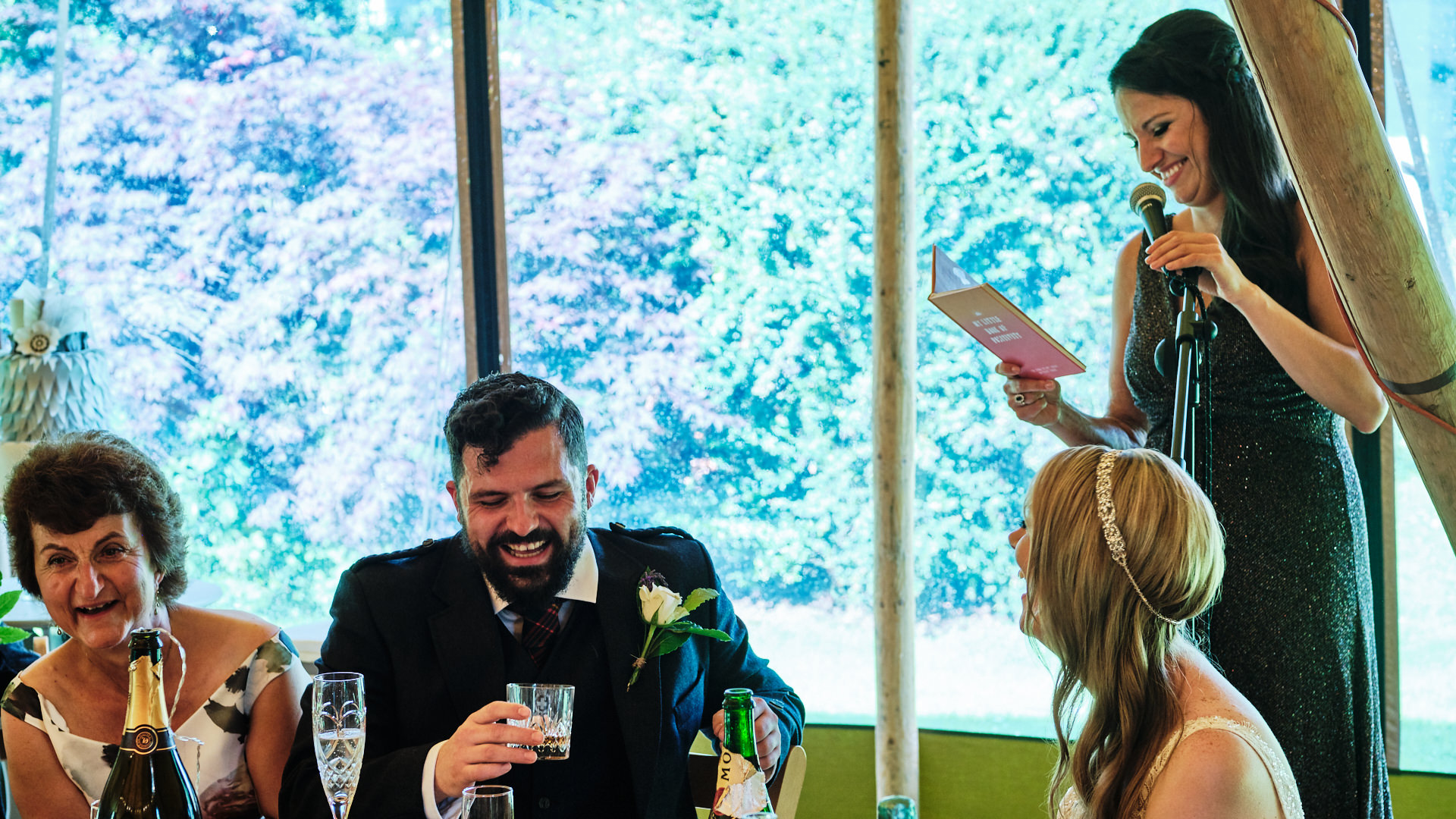 colour photograph of the chief bridesmaid giving a speech at a wedding while the wedding party are laughing