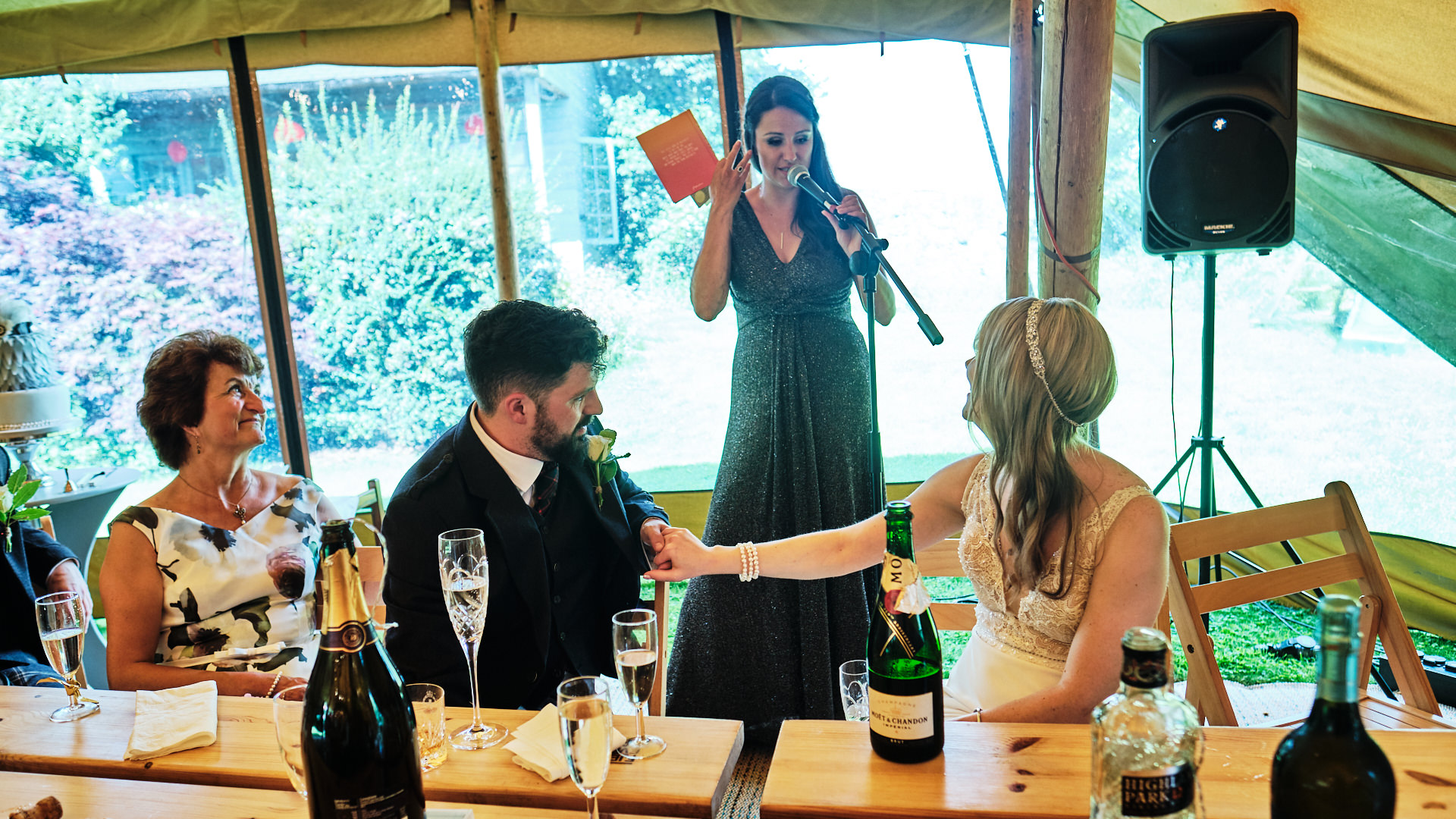 colour photograph of the chief bridesmaid giving an emotional speech at a wedding while the wedding party are in tears